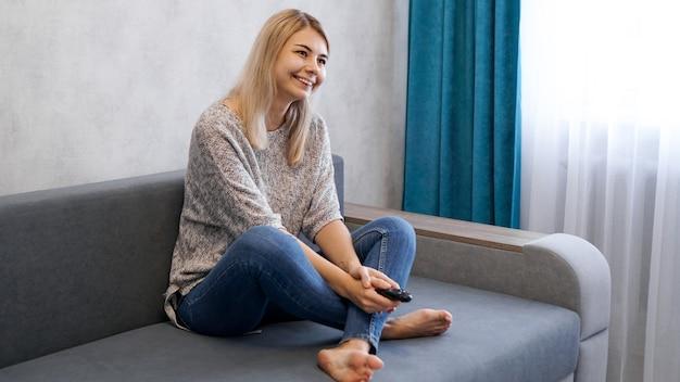 Szczęśliwa kobieta oglądając telewizję, siedząc na kanapie w salonie w domu
