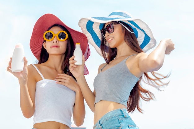 Szczęśliwa kobieta ono uśmiecha się w okularach przeciwsłonecznych trzyma sunscreen płukanki butelki uv pakuje kosmetyka ochronnego.