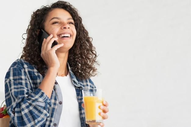 Szczęśliwa kobieta opowiada na telefonie i pije sok