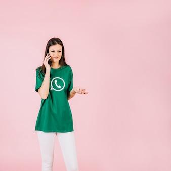 Szczęśliwa kobieta opowiada na telefonu komórkowego wzruszać ramionami