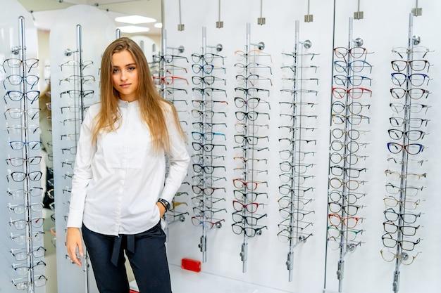Szczęśliwa kobieta optometrysta, optyk stoi z wieloma okularami w sklepie optycznym.