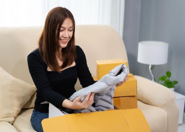 Szczęśliwa kobieta otwiera kartonową paczkę w salonie w domu, zakup w sklepie internetowym