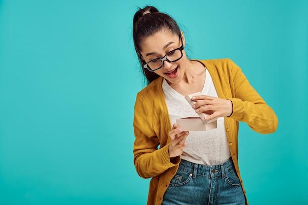 Szczęśliwa kobieta otwiera pudełko, niebieska ściana, pozytywne emocje. wyraz twarzy, osoba płci żeńskiej, patrząc na kamery w studio, koncepcja emocjonalna, uczucia