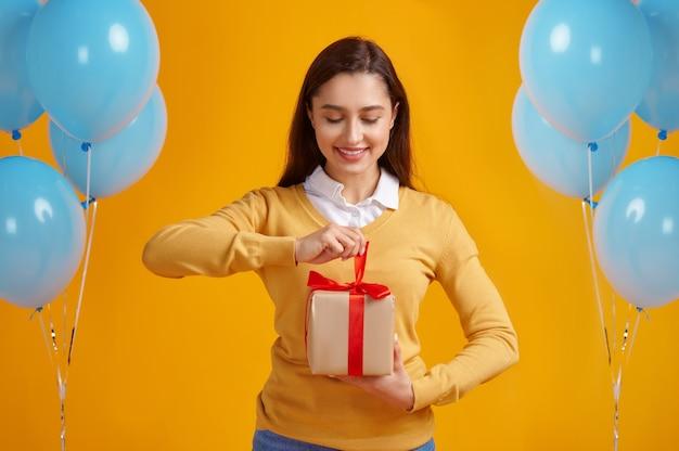 Szczęśliwa kobieta otwiera pudełko z czerwonymi wstążkami, żółte tło. ładna osoba płci żeńskiej dostała niespodziankę, imprezę lub uroczystość urodzinową, dekorację balonów