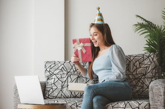 Szczęśliwa kobieta otwierająca pudełko prezentowe i czująca się zaskoczona podczas nowej normalnej imprezy bożonarodzeniowej online w domu na kanapie za pośrednictwem laptopa