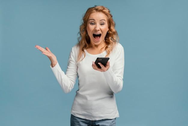 Szczęśliwa kobieta patrząc na telefon komórkowy