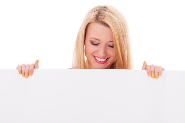 Szczęśliwa kobieta patrząc w dół na pustej tablicy