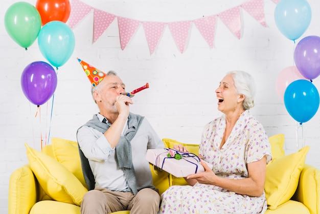 Szczęśliwa kobieta patrzeje jej męża dmuchania przyjęcia róg z prezentem urodzinowym