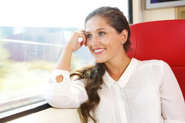 Szczęśliwa kobieta patrzeje z taborowego okno