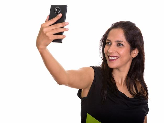 Szczęśliwa kobieta perski uśmiechając się podczas robienia selfie