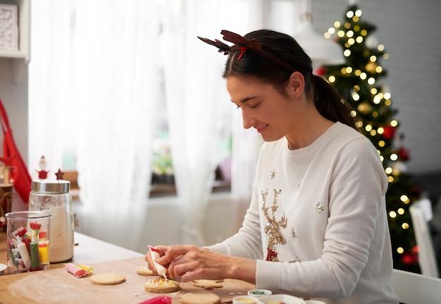Szczęśliwa kobieta pieczenia ciasteczek na boże narodzenie