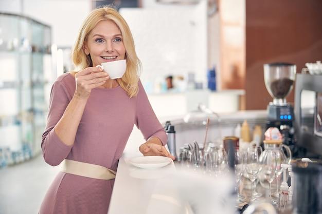 Szczęśliwa kobieta pijąca aromatyczną kawę podczas przerwy w kawiarni, zachowując uśmiech na twarzy