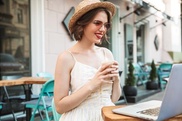 Szczęśliwa kobieta pije kawę w sukni i słomkowym kapeluszu