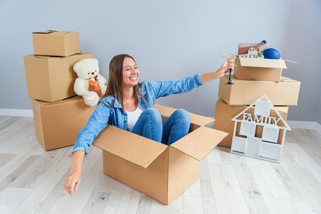 Szczęśliwa kobieta pije szampana ze szkła, siedząc w kartonowym pudełku w nowym mieszkaniu.