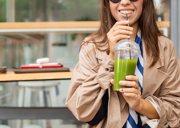 Szczęśliwa kobieta pije zielony koktajl