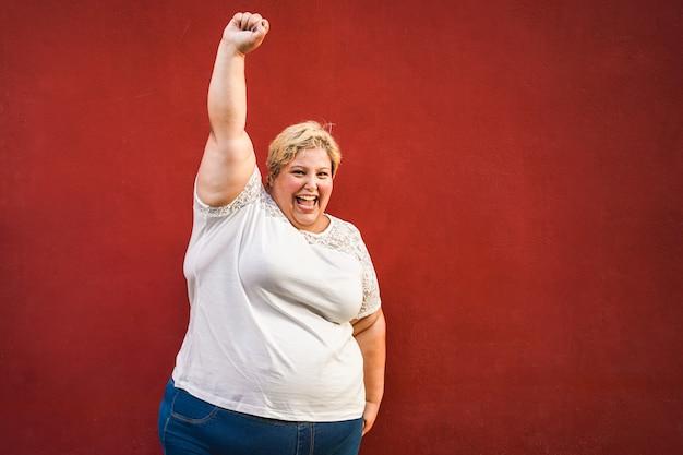 Szczęśliwa kobieta plus-size świętuje i tańczy dla kobiecej mocy