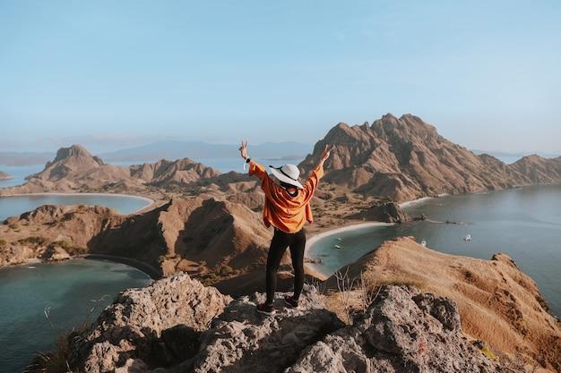 Szczęśliwa kobieta podróżnik w letnim kapeluszu stojąca podczas pozowanie na szczycie góry skalnej