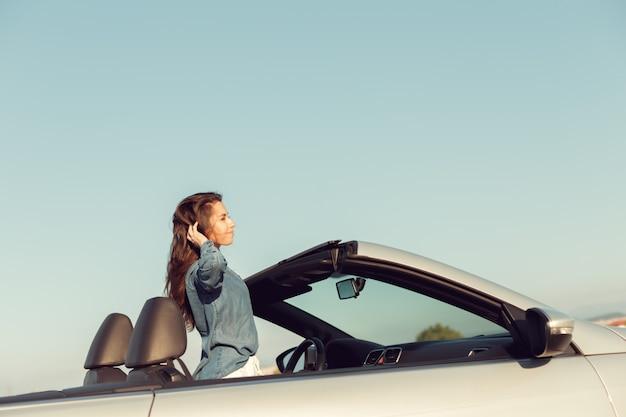 Szczęśliwa kobieta podróżnik w samochodzie cabrio