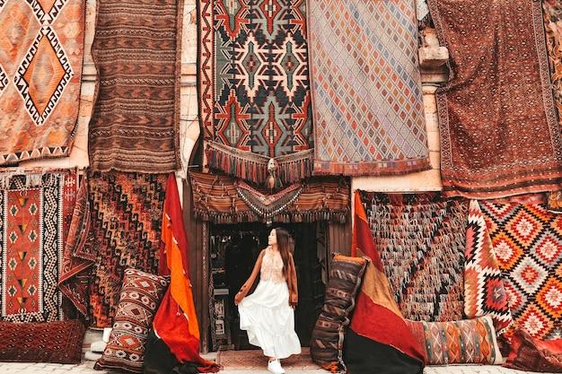 Szczęśliwa kobieta podróżująca z niesamowitymi kolorowymi dywanami w lokalnym sklepie z dywanami, göreme. kapadocja turcja