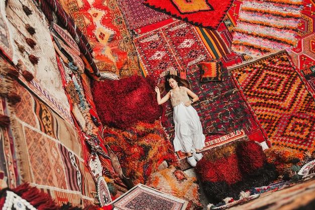 Szczęśliwa kobieta podróżująca z niesamowitymi kolorowymi dywanami w lokalnym sklepie z dywanami, göreme.