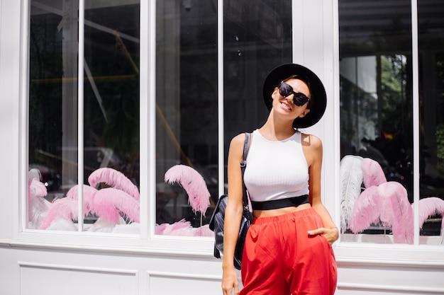 Szczęśliwa kobieta podróżuje po bangkoku z plecakiem, ciesząc się pięknym słonecznym dniem, stojąc przy ścianie i oknie kawiarni