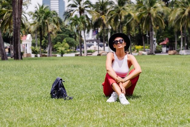 Szczęśliwa kobieta podróżuje po bangkoku z plecakiem, ciesząc się pięknym słonecznym dniem w tropikalnym parku na zielonej trawie