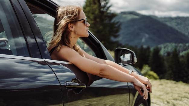 Szczęśliwa kobieta podróżuje samochodem po górach. koncepcja wakacji letnich. kobieta za oknem, ciesząca się widokiem na góry