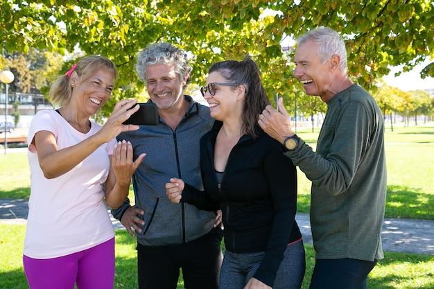 Szczęśliwa kobieta pokazuje ekran telefonu komórkowego do kolegów z klubu fitness. radosnych dojrzałych przyjaciół stojących razem po porannych ćwiczeniach w parku. koncepcja emerytury lub komunikacji
