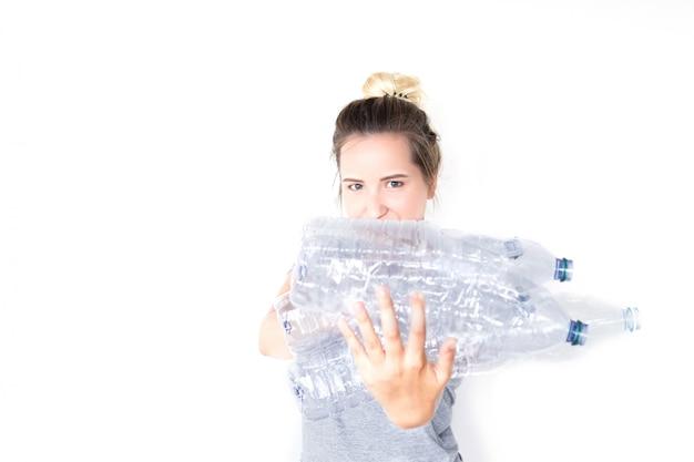 Szczęśliwa kobieta pokazuje i trzyma przetwarzającą plastikową butelkę odizolowywająca. efekt rozmycia. koncepcja recyklingu. oddzielna zbiórka odpadów