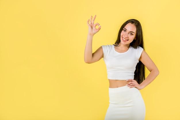 Szczęśliwa kobieta pokazuje ok znaka