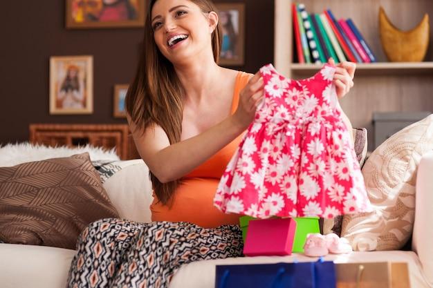 Szczęśliwa kobieta pokazuje sukienkę dla małej dziewczynki