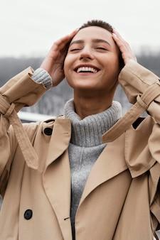 Szczęśliwa kobieta pozowanie na zewnątrz średni strzał