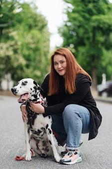 Szczęśliwa kobieta pozuje i bawi się ze swoim dalmatyńczykiem podczas miejskiego spaceru po mieście