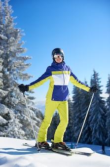 Szczęśliwa kobieta pozuje na nartach przed jazdą na nartach. słoneczny dzień w ośrodku narciarskim. jasne błękitne niebo, pokryte śniegiem jodły na tle.