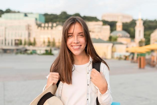 Szczęśliwa kobieta pozuje na zewnątrz z kapeluszem i plecakiem