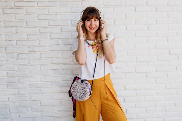 Szczęśliwa kobieta pozuje nad białym murem ze słuchawkami.