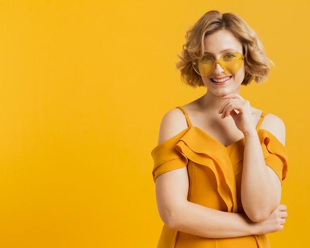 Szczęśliwa kobieta pozuje podczas gdy będący ubranym okulary przeciwsłonecznych