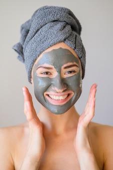 Szczęśliwa kobieta pozuje podczas gdy będący ubranym twarzy maskę
