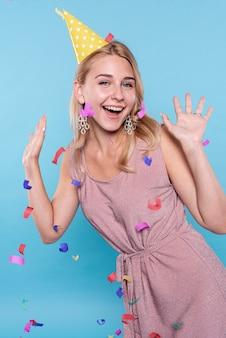 Szczęśliwa kobieta pozuje podczas gdy confetti latać