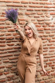 Szczęśliwa kobieta pozuje podczas gdy trzymający bukiet lawendowi kwiaty