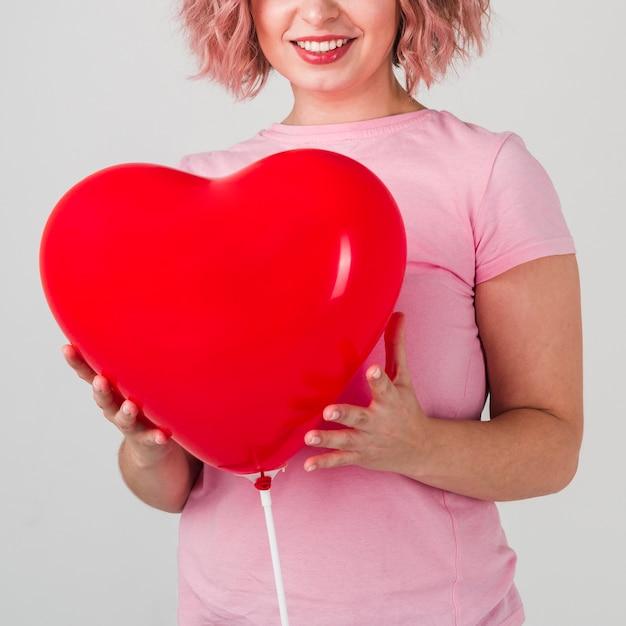 Szczęśliwa kobieta pozuje z balonem