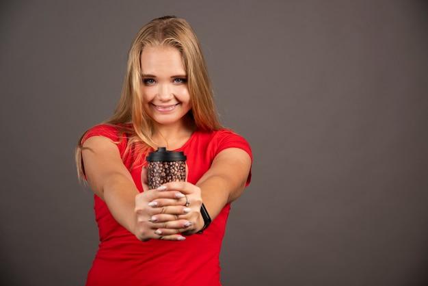 Szczęśliwa kobieta pozuje z kawą na wynos na czarnej ścianie.