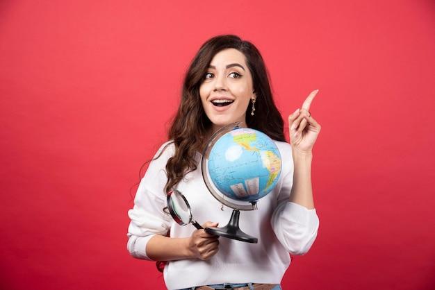 Szczęśliwa kobieta pozuje z kulą ziemską i lupą, jednocześnie wskazując w górę. zdjęcie wysokiej jakości