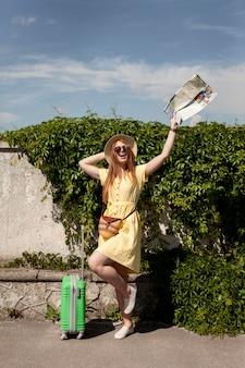 Szczęśliwa kobieta pozuje z mapą