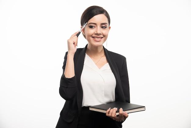 Szczęśliwa kobieta pozuje z notatnikiem na białym tle. zdjęcie wysokiej jakości