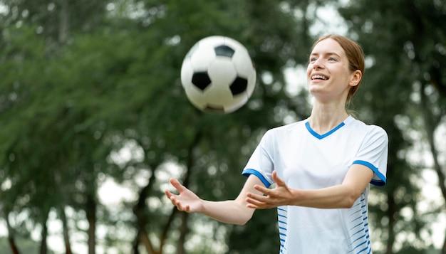 Szczęśliwa kobieta pozuje z piłką