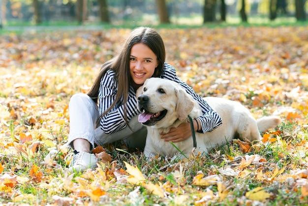 Szczęśliwa kobieta pozuje z ślicznym psem