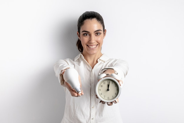 Szczęśliwa kobieta pozuje z żarówką i zegarem