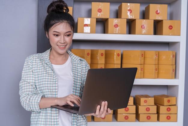 Szczęśliwa kobieta pracuje z laptopu i kuriera pakuneczka pudełkiem w domu biuro