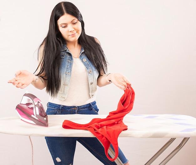 Szczęśliwa kobieta prasowanie odzieży żelazkiem elektrycznym na białym tle